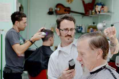 Tom Martin (in chair) of Towson, Steve Rowell, owner of Hairway to Steven, on York Road, with barber Charlie Helmlinger (background) and Eric Denicolos, a freshman at Towson University. The four were talking Orioles baseball at the shop on Wednesday.