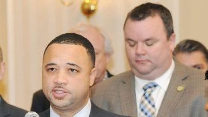 Antonio Hayes speaks at a news conference, with Del. Eric Bromwell behind him