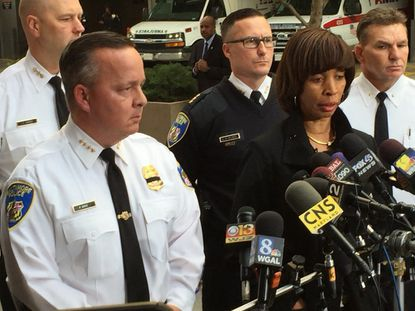 Baltimore police commissioner Kevin Davis (left) and Mayor Catherine Pugh (right) announce that Det. Sean Suiter, 43, has died after being shot in West Baltimore.