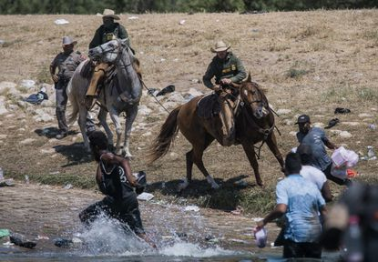 U.S. Customs and Border Protection mounted officers attempt to contain migrants as they cross the Rio Grande from Ciudad Acuna, Mexico, into Del Rio, Texas, Sunday, Sept. 19, 2021. (AP Photo/Felix Marquez)