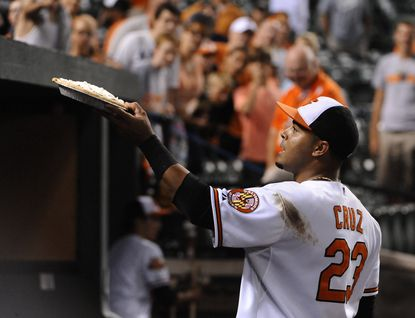 Designated hitter Nelson Cruz, who hit a game-tying grand slam in the eighth inning, gives a pie to fans above the dugout after the Orioles' 5-4 win over the Chicago White Sox in 12 innings at Camden Yards.