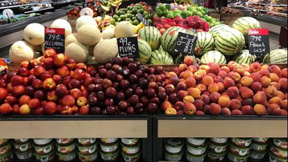 Through a new partnership with Lyft, Baltimore is hoping to make it easier and cheaper to connect people in low-income neighborhoods with healthy food. In this 2018 file photo, nectarines, plums, mangoes and peaches are marked at a fruit stand in a grocery store in Aventura, Florida.
