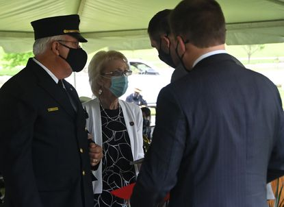Debbie Schaffer, Hanover, PA, speaks with Baltimore County Executive John Olszewski, Jr., during the 36th annual Fallen Heroes Day observance at Dulaney Valley Memorial Gardens. Schaffer's husband, Paramedic Jeffrey Lee ÒJeffÓ Schaffer of the Taneytown Volunteer Fire Company, is remembered for his service. He died on August 10, 2020 of COVID-19 after working as a first responder during the pandemic. May 7, 2021