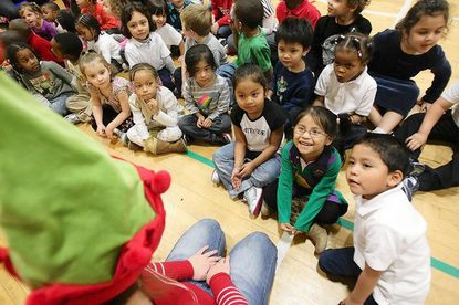 Stephanie Perez-Sedeno, 4, gives Olivia Michael, left, 15, of Lutherville a big smile before members of the youth group from Hunt's Memorial United Methodist Church at Charles Carroll Barrister Elementary School in Baltimore, on Dec. 21.