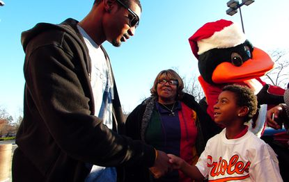 Treated to a shopping spree by Adam Jones, Maurice Malloy shakes hands with the center fielder as his family arrives to shop at a local Target.