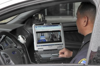 A Baltimore County police officer demonstrates how police can view elementary school security cameras from their patrol cars. Baltimore County unveiled a new OneView system that makes security footage available to county police.