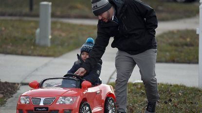 Anthony Hynes of Bel Air teaches his son, Duke Hynes, 3, to steer his new Christmas present, a battery-powered red convertible sports car, on the sidewalk on Wednesday, Dec. 27.