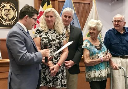 Brenda Hiob Moore, second from left, is with members of her family in Aberdeen City Hall Monday as Mayor Patrick McGrady reads a proclamation honoring Moore for her 42 years of service as the city Board of Appeals' court reporter.