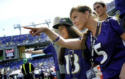 Ava Luhn, 8, of Westminster, and her mother Lisa Luhn watch warm-ups on the field from the Ravens sideline before the Baltimore Ravens' home opener against the Cleveland Browns at M&T Bank Stadium in Baltimore Sunday.