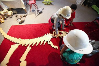 Ruby Colandrea, 6, of Greenbelt and her brother Gus, 4, work a dinosaur puzzle with their friend Kohl Green, 5, of Beltsville (front), part of the hands-on dinosaur exhibit in the Carriage House at Montpelier Mansion.