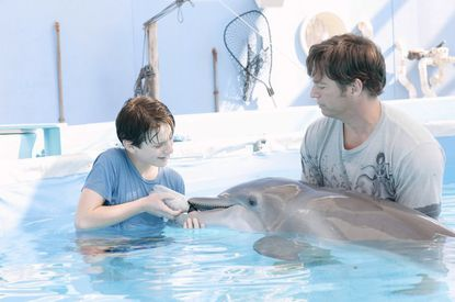"""Nathan Gamble as Sawyer attends to his new friend Winter with the help of Dr. Clay Haskett (Harry Connick Jr.) in the new family adventure """"Dolphin Tale,"""" now playing at area theaters."""