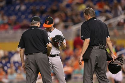 """Brian Matusz of the Orioles is ejected by umpire Paul Emmel for having a """"foreign substance"""" on his arm during the 12thinning against the Miami Marlins at Marlins Park on May 23, 2015 in Miami. Matusz has been suspended eight games."""
