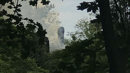 Smoke can seen from the abandoned Victorian house on Frederick Road Thursday afternoon.