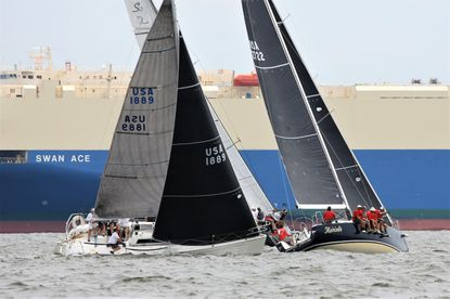 M'am'selle, a J/122 skippered by Ed Hartman, crosses Monkey Dust (Tripp 33, Craig Saunders) as the ORC fleet competes in the AYC Annual Regatta on the Chesapeake Bay with an anchored freighter as a backdrop.