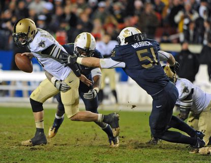 Navy linebacker Matt Warrick pursues Army quarterbaack Trent Steelman during last year's game. Warrick's father, Vince, graduated from West Point in 1980 and spent 12 years in the Army, ultimately as a helicopter pilot.
