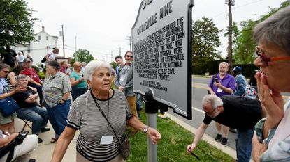 Margarita Melville, a member of the Catonsville Nine, stands next to a state sign unveiled Saturday to recognize the activists' 1968 protest. The nine stormed a local draft office, stole draft records and burned them. They were convicted and sentenced to federal prison.