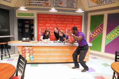"From left: Megan Anderson, Eric Messner, and Liliana Evans as sub shop workers making sandwiches as franchise owner Gary Fletcher keeps time with a stopwatch in ""American Hero"" at Rep Stage."