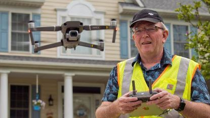Drone pilot Shawn MacWilliams steadies his Mavic Pro 2 before documenting a home via drone.