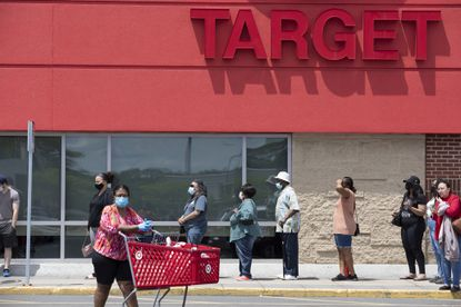 In this May 30, 2020 photo, people in protective masks line up to enter a Target, in Boston, amid the coronavirus pandemic.
