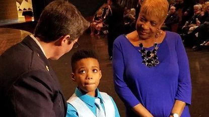 DJ Goodman, center, was awarded the Baltimore County Fire Department's highest civilian honor at a ceremony March 26 for alerting his grandparents to a house fire last year when he was just nine years old.