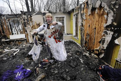 Chris Ellis holds up sports jerseys, including one with the name McGregor, while sorting through the remains of his burned-out Hampton home. Former Orioles pitcher Scott McGregor, a neighbor, has offered to let the Ellis family stay in his house while he and his wife are in Florida for spring training. McGregor is coordinating rehab programs for injured minor-league pitchers this season.