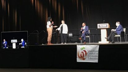 A high school student asks BGE CEO Calvin Butler, seated center with microphone, a question at the Maryland Council on Economic Education's financial literacy for youth awards luncheon.
