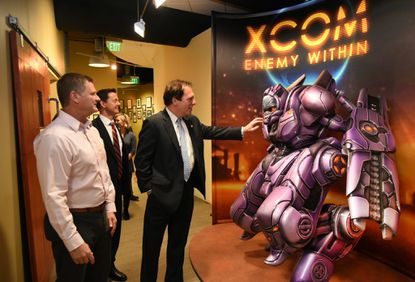"Hunt Valley, MD - December 7, 2015 - Firaxis Games president Steve Martin, left, gave a tour of the expanded studio to Baltimore County officials, including Will Anderson, director of Baltimore Economic and Workforce Development, second from left, and county executive Kevin Kamenetz, who paused to touch the display for ""XCOM Enemy Within."" Firaxis, the biggest video gaming company in the Hunt Valley and Timonium area, started in 1996 with 13 people. They recently expanded to 40,000 square feet at their Hunt Valley studio to accommodate today's 180 employees."