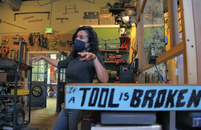 """Lynn McCann, director of development, gestures among a room filled with borrowable tools in the Station North tool library in a building called """"Area 405,"""" which is now for sale Tue., June 22, 2021. (Karl Merton Ferron/Baltimore Sun)."""