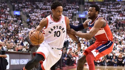 The Raptors' DeMar DeRozan drives toward the net as the Wizards' John Wall defends during the first half of Game 5 of a first-round playoff series Wednesday, April 25, 2018, in Toronto.