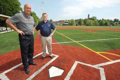 Cal Ripken Jr., lef,t and Steve Salem, President of the Cal Ripken Sr. Foundation, right, tour a new ball field the foundation helped build in Annapolis in 2014.