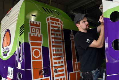 Tommy O'Malley, an installation manager with AP Corporation, wraps a new Charm City Circulator bus in a vinyl coating at the George L. Winfield Fleet Management Facility in east Baltimore. January 30, 2020