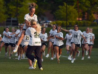 Olivia Rose jumps into the arms of teammate Leah Warehime as their St. Paul's teammates rush the field to celebrate following their victory over McDonogh during the IAAM girls lacrosse championship game on Saturday, May 15, 2021. (Brian Krista/Baltimore Sun Media).