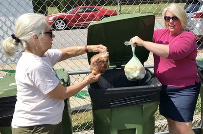Carol Zimmerman, left, president of the Havre de Grace Green Team, and City Councilwoman Casi Boyer prepare to deposit the first pieces of kitchen waste in the new Food Waste Disposal site in Hutchins Park following a ribbon-cutting ceremony last Friday. The food waste disposed of there will be converted into compost.