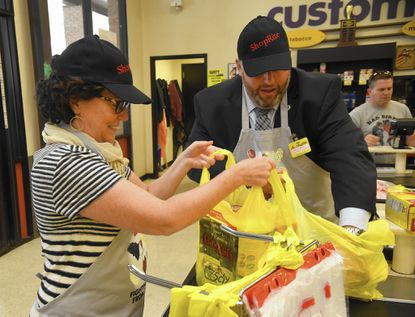 Meg Kimmel, left, with the Maryland Food Bank, and Len Parrish with Harford County Housing and Community Development, bag items for a customer as they participate in the Bagging for Hunger event at the ShopRite grocery store in Forest Hill Wednesday afternoon.