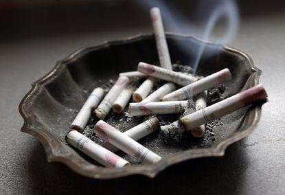 A cigarette burns in an ashtray at a home (AP Photo/Dave Martin).