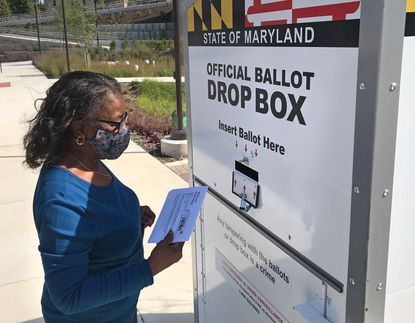 Jeanette Witherspoon casts her ballot at the Board of Elections drop box installed on the Morgan State University campus, on W. Cold Spring Lane near Hillen Road.