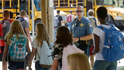 Master Deputy Justin Shriver, South Carroll's school resource officer, looks on as students are dismissed on the first day of school Sept. 4, 2018.