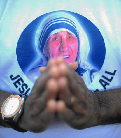 An Indian Christian prays during a special mass in honour of Mother Teresa at the St. Mother Teresa Church in Virar some 72 km north of Mumbai on September 4, 2016, as she was being canonised at the Vatican. Pope Francis on September 4 proclaimed Mother Teresa a saint, hailing her work with the destitute of Kolkata as a beacon for mankind and testimony of God's compassion for the poor. The revered nun's elevation to Roman Catholicism's celestial pantheon came in a canonisation mass in St Peter's square presided over by Pope Francis in the presence of 100,000 pilgrims. / AFP PHOTO / INDRANIL MUKHERJEEINDRANIL MUKHERJEE/AFP/Getty Images ** OUTS - ELSENT, FPG, CM - OUTS * NM, PH, VA if sourced by CT, LA or MoD **