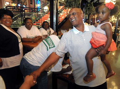 """Baltimore City Council President Bernard C. """"Jack"""" Young, with his 2-year-old granddaughter, Madisyn Lockett, greets supporters Tuesday at his election watch party at Leinenkugel's Beer Garden at Power Plant Live."""