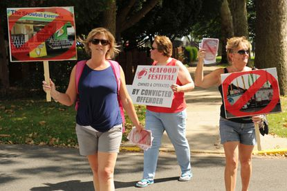 From left, Keri Kateley of Aberdeen, and Debi Callaghan and Debbie Phelan of Havre de Grace hand out fliers regarding Charles Maslin near the festival at Tydings Park in Havre de Grace on Friday, August 7.