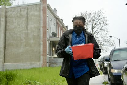 Eshawn Bell carries a container containing personal protective equipment to a home on Cottage Avenue by Sinai Hospital, targeting some of the outreach to vulnerable people in the 21215 ZIP code with chronic health problems.