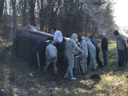 Members of the Georgetown men's basketball team assist a car involved in a crash with the team bus on Monday along I-95 in Howard County.