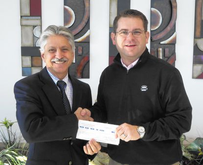 Dr. Tom Zirpoli, left, president and CEO of Target Community & Educational Services Inc., accepts a donation check from Nigel Hayes, general manager of Koons Westminster Toyota Scion.