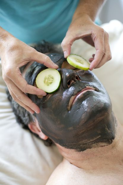 Paramedical esthetician Kelly Anderson covers theeyes of Gordon Lane of Columbia with cucumbers after she applied a black charcoal mask at Brightwater: The Spa at the Skincare Institute.