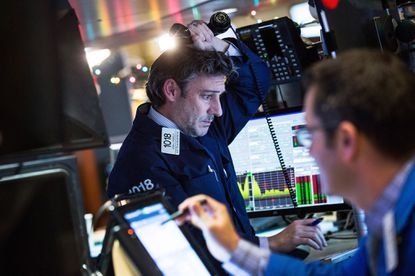 NEW YORK, NY -- A trader works on the floor of the New York Stock Exchange during the afternoon of January 4, 2016 in New York City. Today marks the first day of trading for the New York Stock Exchange; the market dove over 350 points upon opening and closed more than 275 points down.