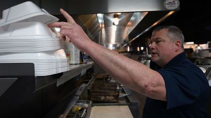 Tom Anuszewski, general manager at Sea King Seafood Market and Pig Picker's BBQ, grabs a foam container as he fills lunch orders. Most of the menu selections are packed in foam containers. The General Assembly passed a bill that will ban polystyrene foam, but Gov. Larry Hogan could veto it. Alternative packaging would add significant cost.
