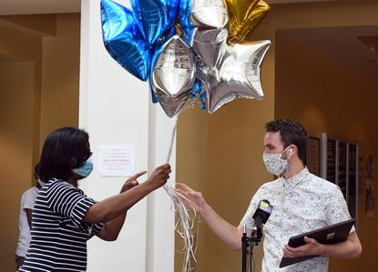 Baltimore City Schools CEO Dr. Sonja Santelises, left, hands a balloon bouqet to Wyatt Oroke, right, a teacher at City Springs Elementary Middle School, who was named Baltimore City Teacher of the Year for 2020. June 26, 2020