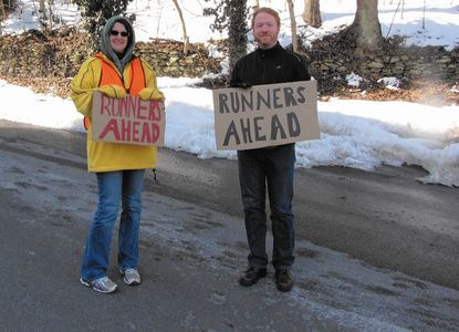 Volunteers Lisa Lance and Bryan Cluts hold signs letting drivers know runners are on the road ahead at the 3rd annual Sykesville Shiver Shuffle, in Sykesville, Feb. 28, 2015. This year's race will be held Saturday, Feb. 27.__- Original Credit: Stephanie Bowman/submitted photo