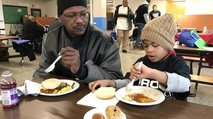 Harold Robertson shares a meal with his 5-year-old son, Donoven, during the 1st Annual City Schools' Fatherhood Engagement Summit Saturday at Frederick Douglass High School.