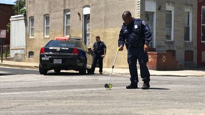 Crime scene technicians at the scene after a Baltimore police officer was hit by a car during a foot chase.